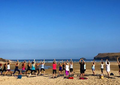 Beach yoga at Polzeath with Wavehunters Fitness