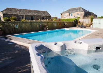 The hot tub and heated outdoor pool at Mesmear, self catering holiday accommodation Polzeath Cornwall