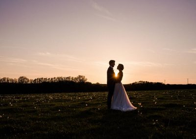 Sunset wedding photograph in a Mesmear field